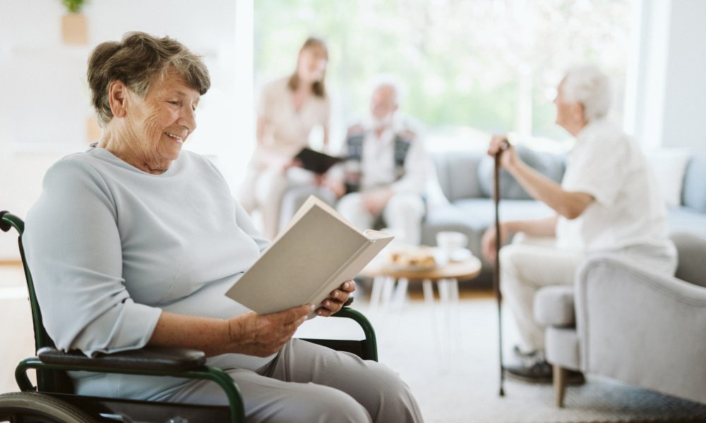 Happy disabled woman reading a book in the nursing home