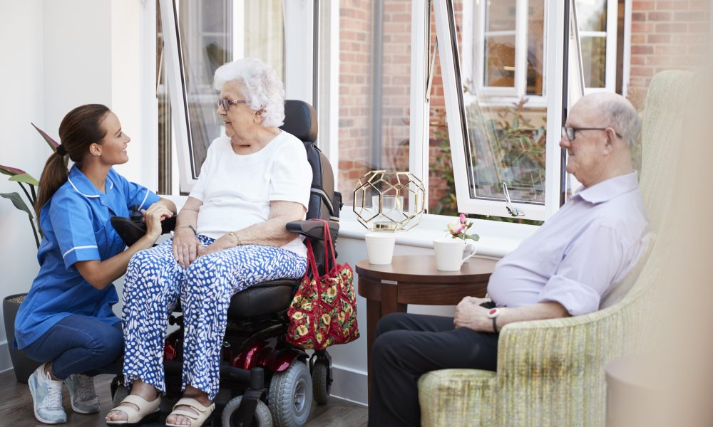 Male And Female Residents Sitting In Chair And Talking With Nurse In Retirement Home