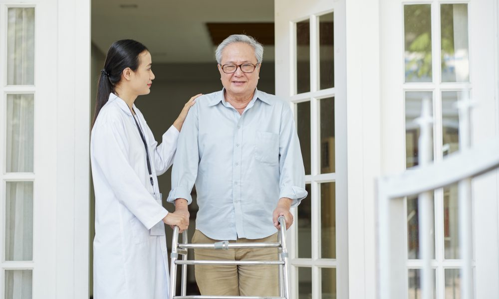Asian senior man in eyeglasses standing with walker near the entrance of his house and trying to go out with his home caregiver