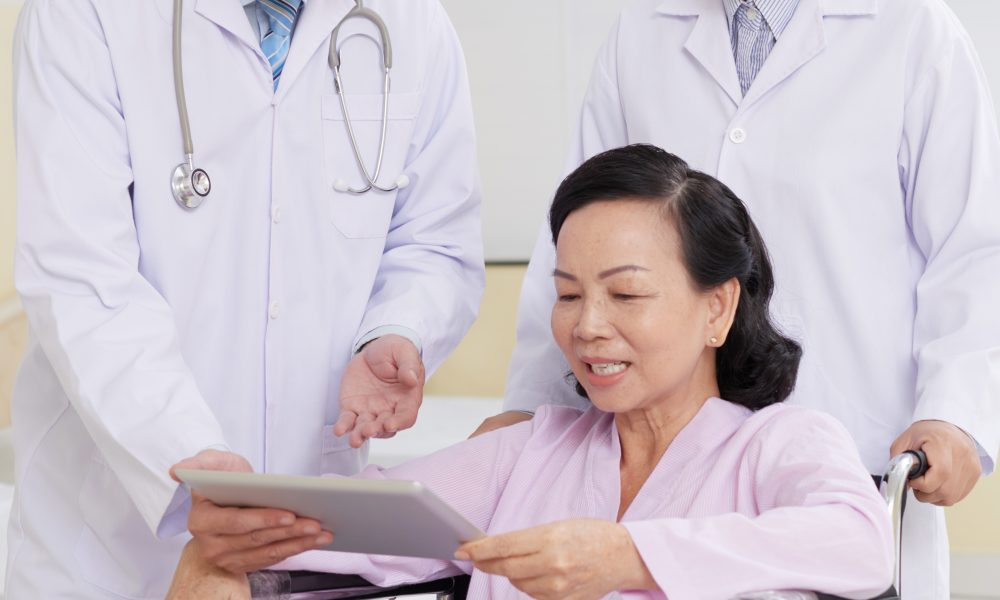 Cheerful aged woman reading doctors presctiption on digital tablet